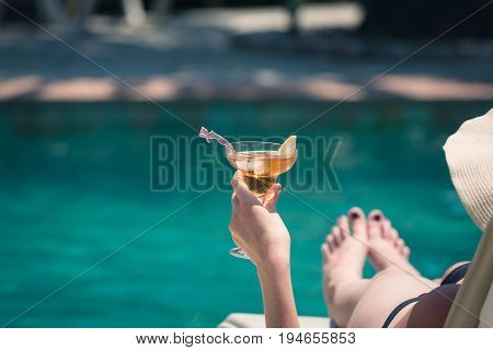Rear view of female lying in sunbed and holding copacabana cocktail at the poolside