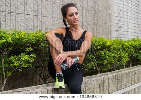 Pretty young female athlete recovering after exercising or running, sitting, listening to music in earphones and looking into the distance.