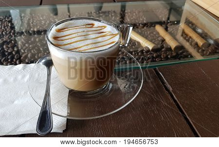 Cappuccino coffee and latte art. A cup of latte cappuccino or espresso coffee with milk put on a wood table with dark roasting coffee beans. Drawing the foam milk on top.