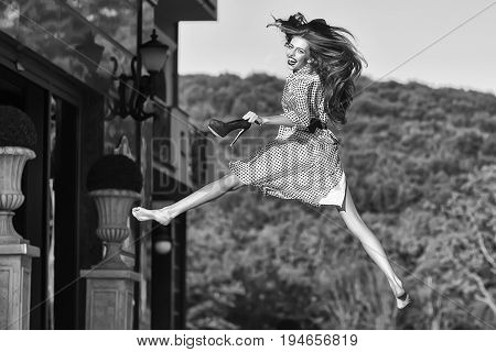 woman or girl with long hair in black and white blouse holding high heeled shoes and jumping retro old vintage black and white style