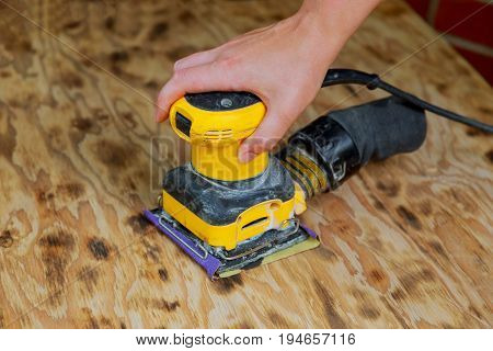 A man working with electrical sanding machine
