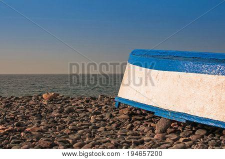 Upturned Fishing Boat on Pebble Beach, blue sky