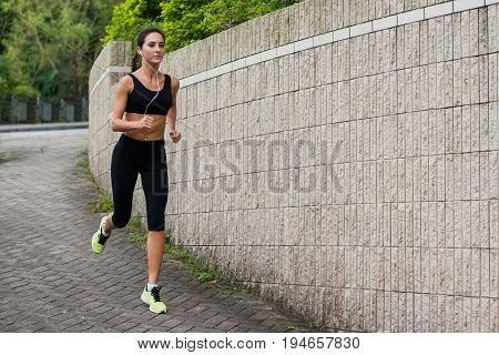 Fit young female jogger jogging on sidewalk in suburban area. Pretty fit girl working out outdoors