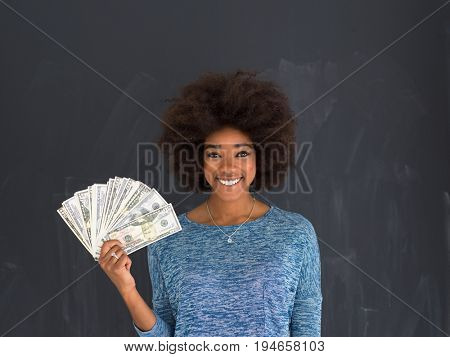 Portrait of a beautiful smiling afro american woman holding money isolated on a gray background