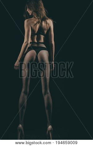 Woman with fit body and long muscular legs wearing black fishnet pantyhose tights and panties in sexy high hell shoes on dark background. Underwear fashion and lingerie. Erotic. Fitness