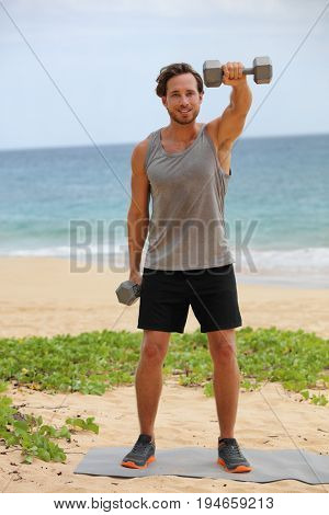 Fitness man lifting dumbbells on beach doing Front Dumbbell Raise i.e. Alternating Front Raise workout for shoulders. Exercising male fitness gym model working out in summer outdoors.
