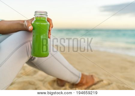 Healthy green juice detox smoothie drink beach woman. Girl holding glass bottle of cold pressed vegetable, juicing trend for nutrition cleanse.