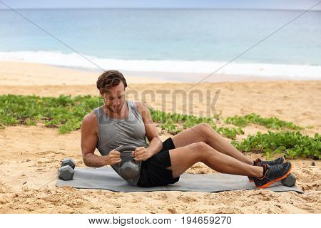 Russian Twist - Fitness man exercising on beach training with kettlebells working out core, obliques and abdominal muscles. Male fitness instructor doing abs exercise working out six pack.
