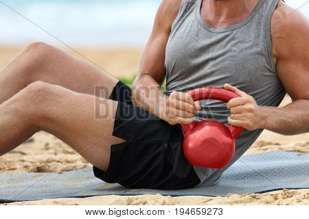 Fitness man lifting kettlebell weight training russian twist exercise. Exercising on beach training with kettlebells working out core, obliques and abdominal abs muscles working out six pack.