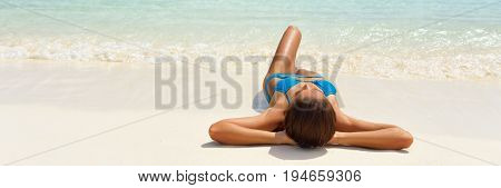 Beach suntan vacation bikini woman lying down tanning under tropical sun in Caribbean. Sexy girl sunbathing banner. Panorama landscape of white sand travel summer holidays. Luxury wellness.