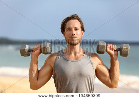 Fitness gym man lifting dumbbell weights. Male athlete with muscular arms with dumbbells overhead doing shoulder press training biceps.