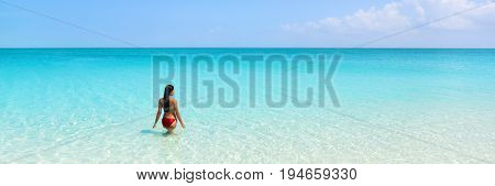 Beach luxury travel getaway resort vacation banner. Bikini woman relaxing enjoying tropical holidays swimming in turquoise ocean water in paradise destination.