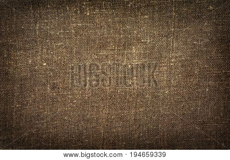 Burlap close-up natural coarse cloth tablecloth with folds.