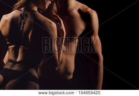 Torsos of woman and man. Muscular male belly and chest with six pack ab and hands with biceps triceps. Sexy girl back in black lingerie on dark background. Passion desire and sex