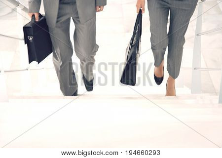 Lowsection of two businesspeople walking up stairs with bags in office