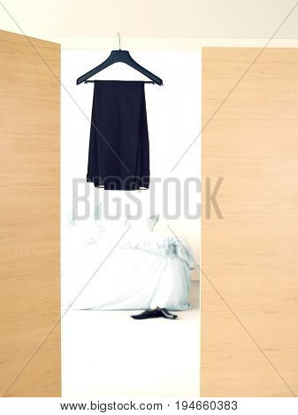 Black dress on hanger in doorway of bedroom at home