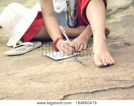 Closeup lowsection of a mixed race young woman sitting on rock and writing