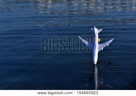Airplane white miniature toy model falling down into blue water of ocean on natural background flight crash and breakdown concept copy space