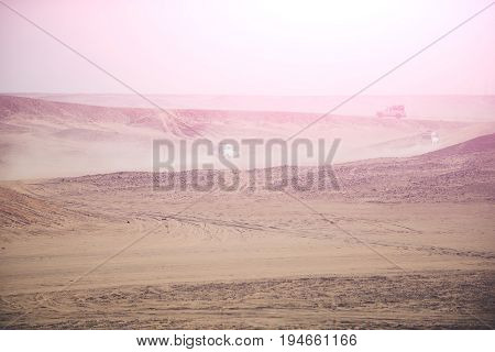 Safari on jeeps in desert. Sand barchans on dusty sky background. Arid landscape. Dune bashing. Offroad adventure. Extreme activity. Travel travelling and trip. Summer vacation