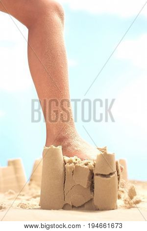 Low section of girl's leg stepping on sand castle at beach