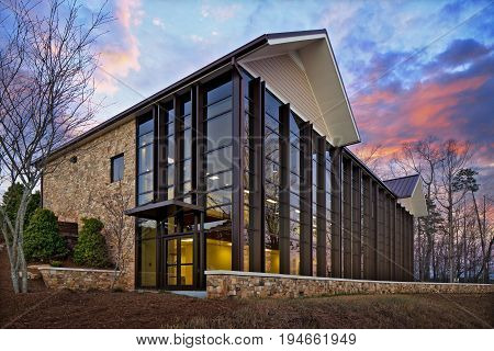 Modern Brick and Glass Home or Office or Retail building exterior in the woods at sunset