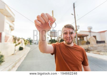Concept of housewarming, real estate, new home - Young man holding key of new house