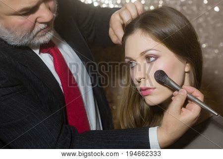 visagiste man or professional makeup artist in business suit applying powder with brush on pretty girl or cute woman face skin. Fashionable model with long hair in beauty salon. Visage