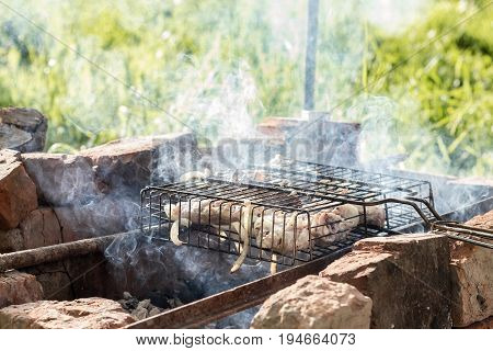 Preparing meat on a steel grate for grill. Smoke from the hot coals. Outdoor cooking