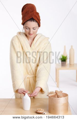 Attractive female teenager in bathrobe, pushing moisturizing bottle, looking down, smiling.