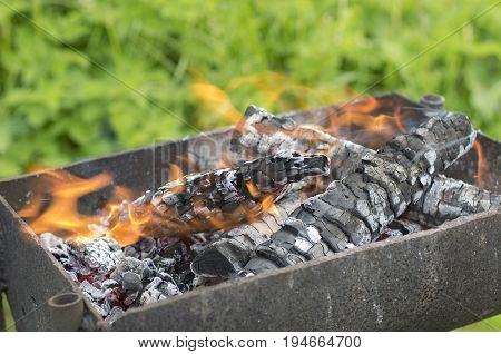 Smoky and blazing firewood in a brazier almost turned into coals