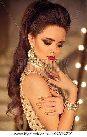Beautiful Brunette Girl Fashion Portrait With Beauty Makeup. Fashionable Luxury Golden Jewelry. Long