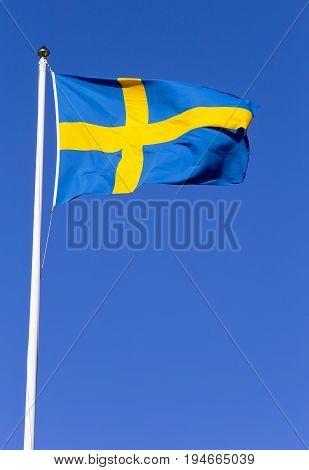 Swedish flag hoisted on a flagpole against a blue sky.