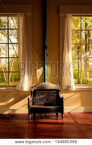 An interior symmetrical image of a dusty vintage gas heater with open windows and spring weather in the background