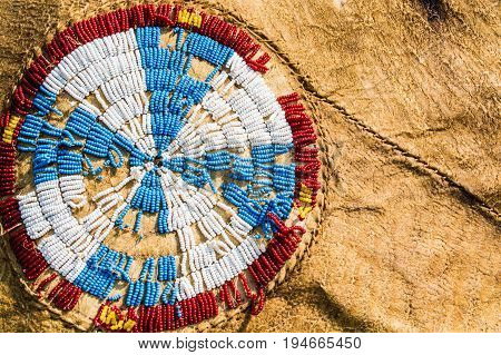 Red white blue and yellow Native American beads are sewn in a cross pattern on a buffalo hide