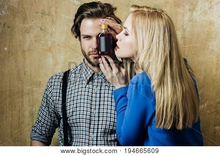 Girl and macho posing with liqueur bottle. Adorable woman with blond long hair and handsome man on beige background. Alcohol appetizer addictive and convive. Unhealthy lifestyle and bad habits