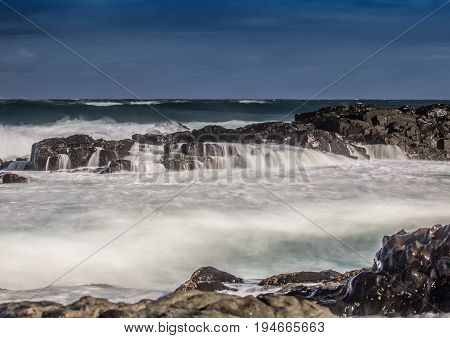 Long Time Exposure Of Waves Around Rocks At The Wild Coast At The Indian Ocean In South Africa