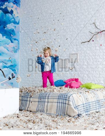 A beautiful child enjoying life. Child jump on bed and fight with pillow