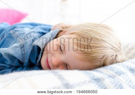 Adorable little girl lay on the bed. Cute girl photo.