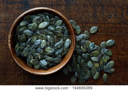 Peeled Dry Pumpkin Seeds In Dark Wooden Bowl Isolated On Dark Brown Wood From Above. Spilled Seeds.