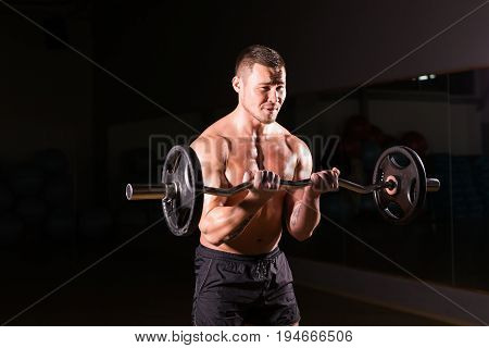 Confident muscular man training with barbells . Closeup portrait of professional bodybuilder workout with barbell at gym