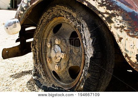 A worn flat vintage tire mounted on an antique truck
