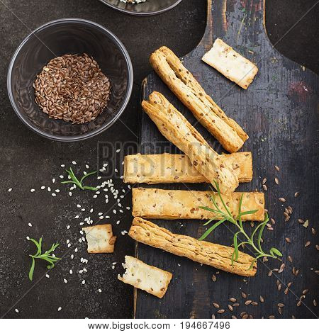 Bread sticks from puff pastry with flax seeds, sesame seeds, sea salt and rosemary on a dark background. Top View