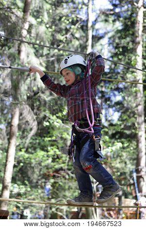 Child Climbing In Adventure Rope Park
