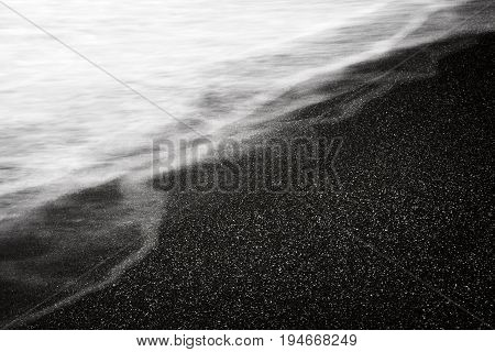 Dark sand and sea wave long exposure abstract textural Black White background