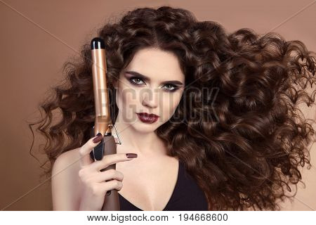 Hairdresser. Curly Hair. Beautiful Brunette Woman Portrait With Long Wavy Hair Ironing It, Using Cur
