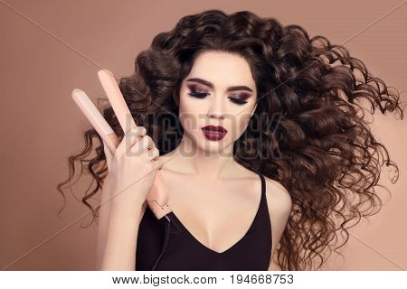 Curly Hair. Beauty Close-up Of Brunette Girl With Blowing Hairstyle Holding Straightening Iron. Mars