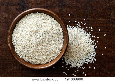 Decorticated Sesame Seeds In Dark Wooden Bowl Isolated On Dark Brown Wood From Above. Spilled Seeds.