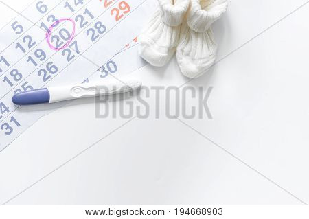 Pregnancy planning. Pregnancy test, calendar and booties on white background top view.