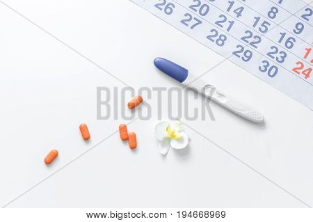 Pregnancy planning. Pregnancy test, calendar on white background top view.