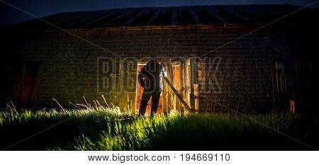 man staring at the light from an abandon barn
